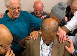 Men pray in group together