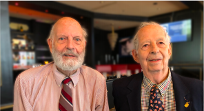 Two well dressed men pose for the camera