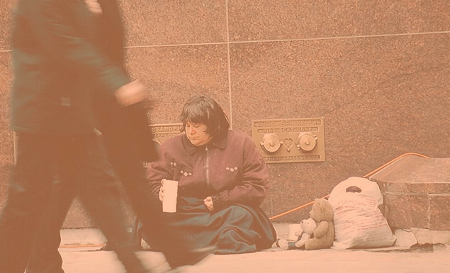 Homeless woman on side of building trying to get change