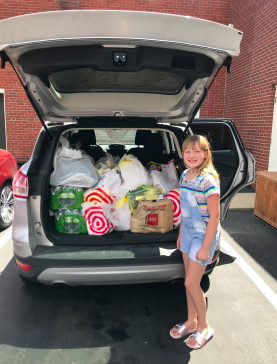 Little girl loads donation groceries into car