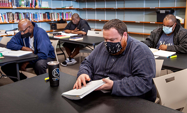 Men studying notebooks in Shelter KC library