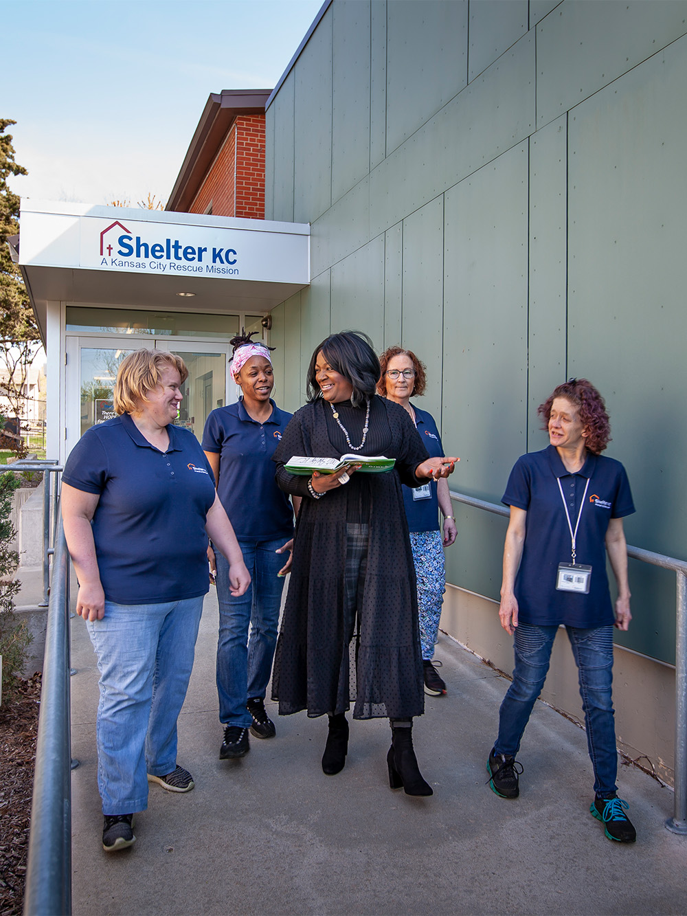 Women from the Shelter KC Women's ministry walk outside while reading bible